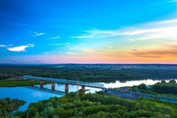 Railway bridge is reflected over the calm White River, surrounded by a green lush forest on the outskirts of the city under the evening blue sky at dusk. Sunset over Ufa, Bashkortostan, Russia.