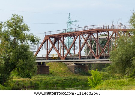 Railway bridge made of iron structures, against a cloudy sky background #1114682663