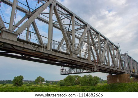 Railway bridge made of iron structures, against a cloudy sky background #1114682666