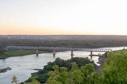 Railway bridge over Belaya river on morning sunrise sky. Sunset over Ufa, Bashkortostan, Russia.