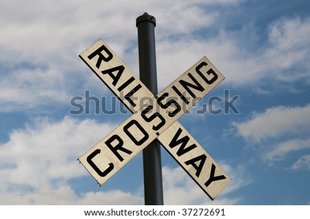 Railway Crossing sign with bright blue sky behind it