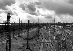 Railway depot panorama with waiting high speed trains and many tracks near main station in Westphalia Germany. Shunting yard on a cloudy day with city silhouettes of Dortmund in the background.