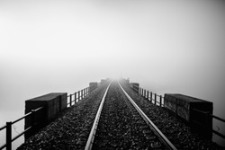 Railway disappearing into the fog. Black and white.