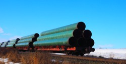 Railway flatcar loaded with large diameter pipe destined for use on the Trans Mountain Pipeline in Western Canada