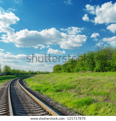 railway goes to horizon in green landscape under blue sky with clouds