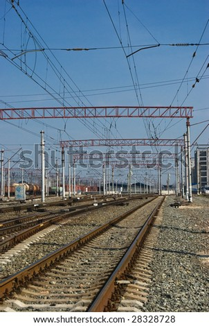 Railway junction. Perspective of crossing rails, traffic lights and train.