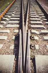 Railway junction tracks in the city with track bed. Gravel and switch at a railroad crossing.