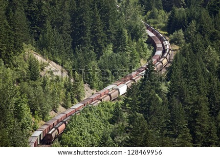 Railway line - long freight trains with tankers and containers runs through curves in the mountain forest, (Fraser Canyon), British Columbia, Canada