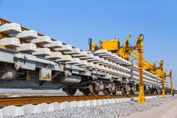 Railway or railroad construction site, railroad track installation machine is in use - Perspective view of Concrete railroad ties in railway construction site