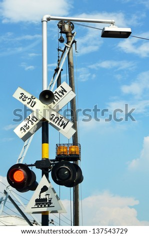 railway sign and traffic lights at a railroad crossing in Thailand