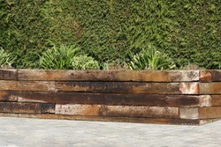 Railway sleepers forming raised bed with green shrubs against hedge background
