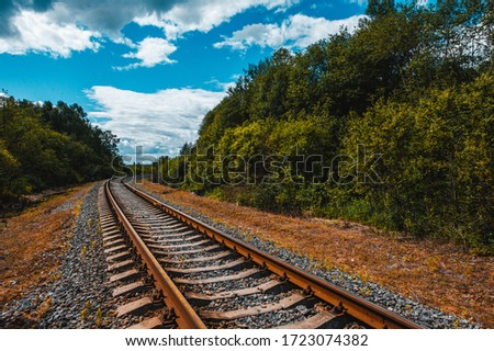 Photo of  Railway station against beautiful colorful sky at sunset. Industrial landscape with railroad, blue sky with clouds in summer .Railway junction in the evening. Railway platfform. Transportation