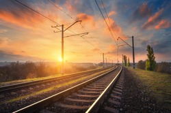 Railway station against beautiful sky at sunset. Industrial landscape with railroad, colorful blue sky with red clouds, sun, trees and green grass. Railway junction. Heavy industry. Evening in autumn