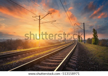 Railway station against beautiful sky at sunset. Industrial landscape with railroad, colorful blue sky with red clouds, sun, trees and green grass. Railway junction. Heavy industry. Evening in autumn #513158971