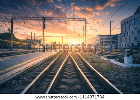 Railway station and beautiful colorful sky at sunset. Industrial landscape with railroad, blue sky with red and orange clouds in dusk. Railway junction in the evening. Railway platfform.Transportation