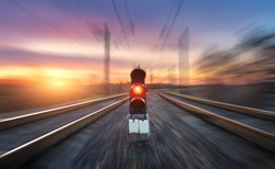 Railway station and semaphore with motion blur effect against colorful sky with clouds at sunset. Concept industrial landscape. Railroad. Railway platform with traffic light. Heavy industry background
