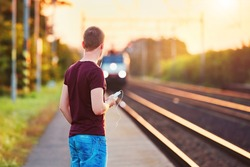 Railway station at the sunset. Young man with smart phone in hand is waiting for the train.