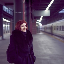 Railway station. Beautiful girl is standing on platform and waiting for train. Woman travels light in evening. Middle-aged lady in warm clothes and coat smiling