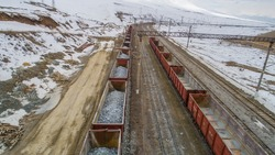 Railway station in mining industry. Freight train open wagons with ore. Train transportation on railway with mine stones at a snowy winter day in mountainous landscape. Full and empty containers