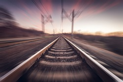 Railway station on the background of blue sky at sunrise with motion blur effect in vintage style. Railroad in Ukraine.