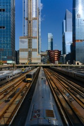 """Railway Station (Penn Station) West Side Yard (Hudson Yards) in Manhattan New York with Trains and new Skyscrapers, """"Vessel"""" spiral staircase. Seen from High Line viewpoint on a sunny blue sky day."""