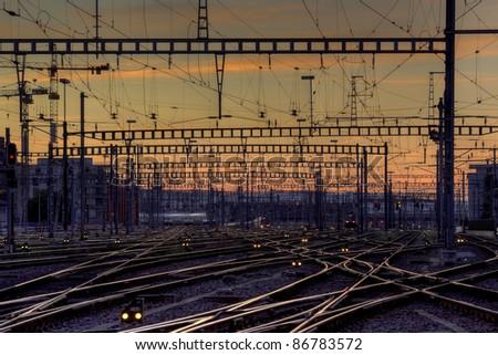 Railway station tracks at dusk - stock photo
