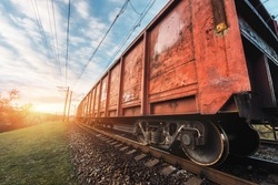 Railway station with cargo wagons and train against sunny sky with clouds in the evening. Colorful industrial landscape. Railroad with vintage toning. Railway platform. Heavy industry. Cargo shipping