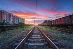 Railway station with freight trains and multicolored buildings at sunset. Railroad in summer. Heavy industry. Landscape with train, railway platform, sky with colorful clouds at dusk. Transportation