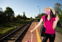 Railway station. Young woman in a protective mask. Safe vacation. A trip on the Polish railway line.