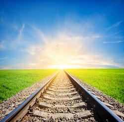 Railway to the sun through green field