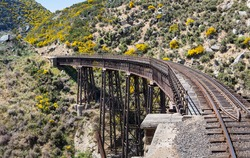 Railway track of Taieri Gorge tourist railway crosses a steel trestle bridge across a ravine on its journey up the valley