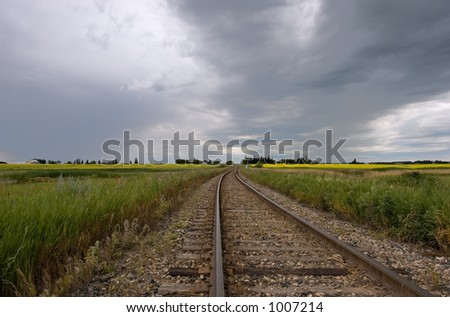 Railway tracks and dark clouds - stock photo
