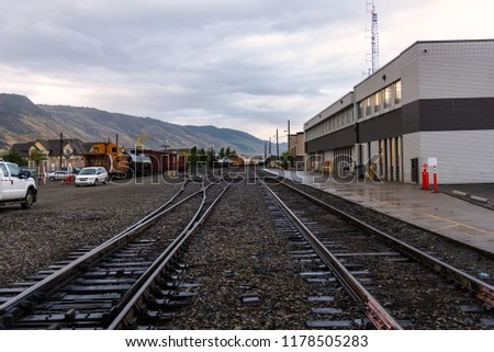 Railway tracks and Freight Cars in a Station under Cloudy Sky at Sunset #1178505283