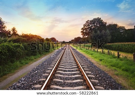 railway tracks in a rural scene with nice pastel sunset #58222861