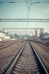 Railway tracks in the city with track bed. Gravel and switch at a railroad crossing.