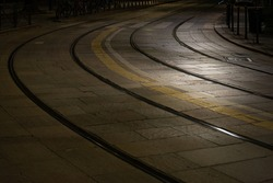Railway tracks of an urban tramway in the night, on a cobblestone ground, Milan, Italy. Rails are bending in a curve. Street lamp spotlight on the right.