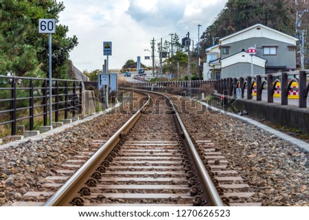 Railway tracks of the Himi-Takaoka coastal line operated by JR West, Amabarashi, Toyama, Japan. TRANSLATION OF TEXTS - LEFT: End of tsunami evacuation zone, RIGHT - Iwasaki bus stop. Сток-фото ©