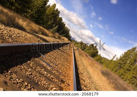 Railway tracks through the rocky mountains - stock photo