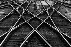 Railway tracks with switches and interchanges at a main line station in Frankfurt Main Germany with geometrical structures, thresholds, gravel and screws. Reflecting symmetrical rails black and white