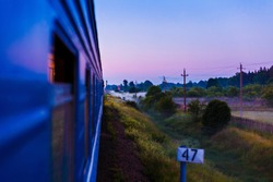 Railway Train moving along beautiful  landscape at sunset in summer Belarus