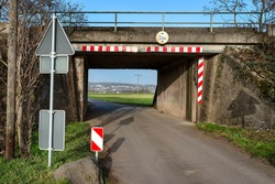 Railway tunnel leading to the road to the farmland, village in the distance and warning signs.