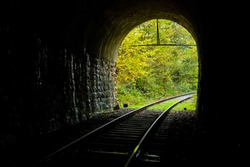 Railway Tunnel Portal with curved track on a small branch line in Sauerland Germany on a autumn day with view out of the darkness into the light at the end of the tunnel