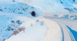 Railway tunnel  with railroad in snowy mountains -The Railway tracks under the snow tunnel