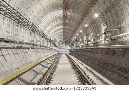 Railway underground tunnel which install running and conductor rail. Selective focus. stock photo