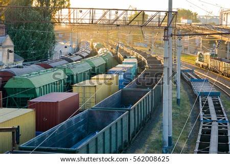 Railways in train parking at the orange sunset panoramic view background. Freight train arrived at the station.