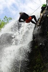 rain adventure spelunking sports canyoning man forest mountains wetsuit water ecuador male descending a enormous falls in ecuadorian rain forest rain adventure spelunking sports canyoning man forest m