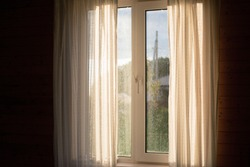 Rain and sun outside the window with curtains