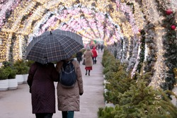 Rain at Christmas holidays, people with umbrella walking on a city street on New Year decorations background. Rainy weather in winter