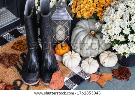 Rain boots on the front porch decorated for autumn with heirloom gourds,  white pumpkins, mums and buffalo plaid welcome mat for an inviting atmosphere.