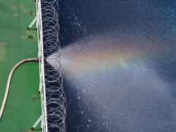 rain bow on water spray from fire hose on a cargo ship which fitted with razor wire during passing piracy high risk area.